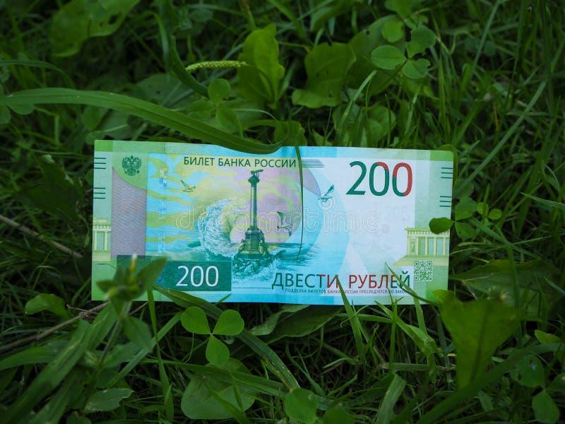 Una nuova banconota russa di duecento rubli che si trovano sulla terra dell'erba verde fotografia stock