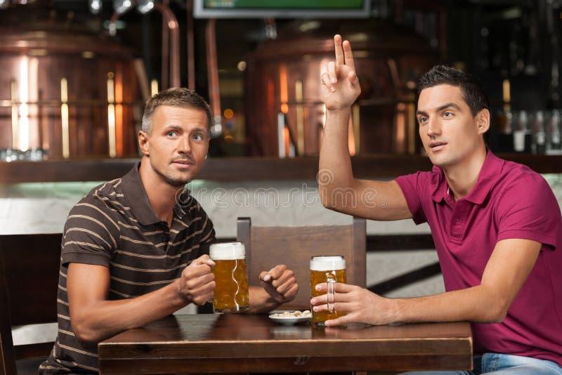 Una nuova birra per favore! Due amici che bevono birra al pub mentre fotografia stock libera da diritti