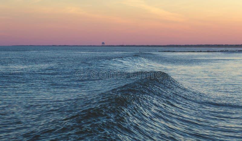 Una ola oceánica en la puesta del sol imagenes de archivo