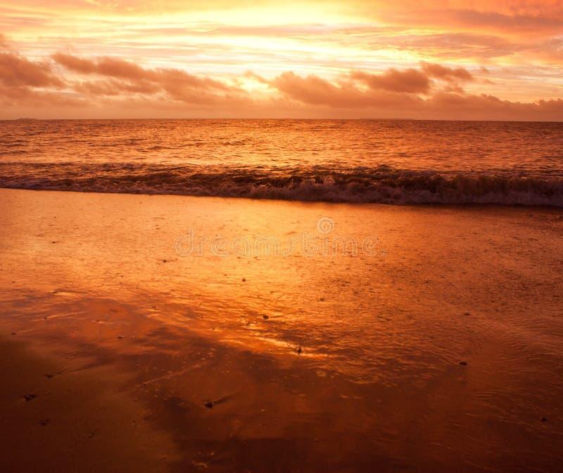 Una onda durante una puesta del sol después de una tormenta en Tonga imagen de archivo