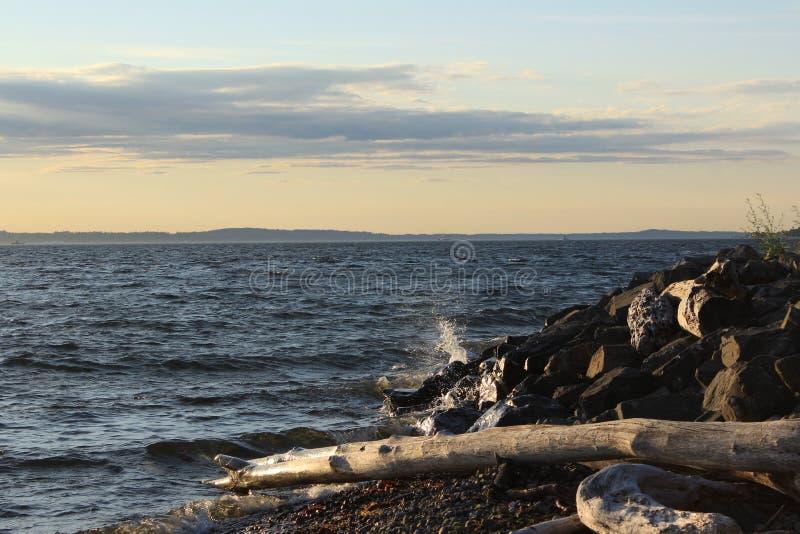 Una onda en Rocky Shore en la puesta del sol foto de archivo libre de regalías