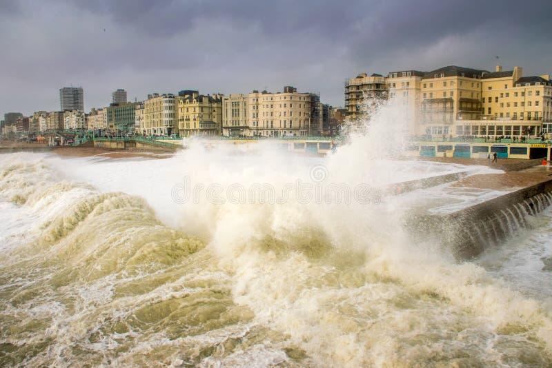 Una onda enorme de Desmond de la tormenta rueda sobre la playa de Brighton que amenaza a la 'promenade' imagenes de archivo