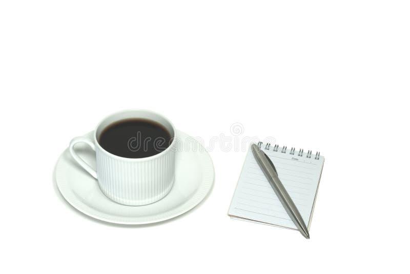 Una opinión de ángulo de una taza de café sólo, de platillo, y de libreta del lado con la pluma, en un fondo exclusivamente blanc fotos de archivo libres de regalías