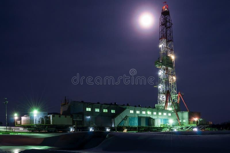Una opinión de la noche de una perforación de la torre de perforación en Siberia imagen de archivo libre de regalías