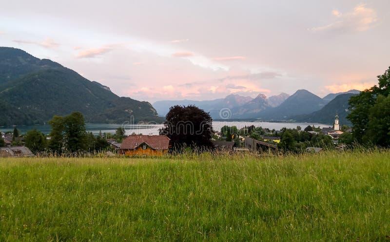 una opinión de la puesta del sol del pueblo en la orilla del lago fotos de archivo libres de regalías
