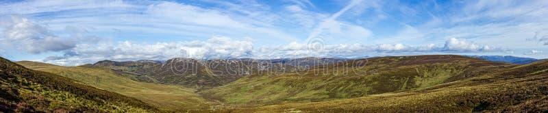 Una opini?n del panorama de un valle escoc?s de la monta?a con el brezo, el camino y la cordillera debajo de un cielo azul majest fotografía de archivo