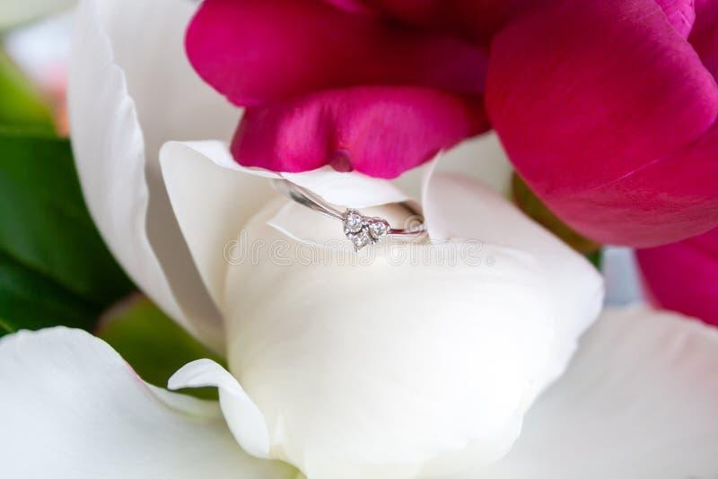 Una opinión del primer de un anillo de compromiso hermoso del oro blanco con tres pequeños diamantes en la forma de un corazón qu imagen de archivo