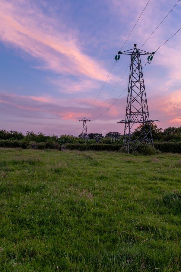 Una opinión del retrato de las líneas eléctricas y de los pilones que llevan apagado en la distancia con una puesta del sol incre imagen de archivo