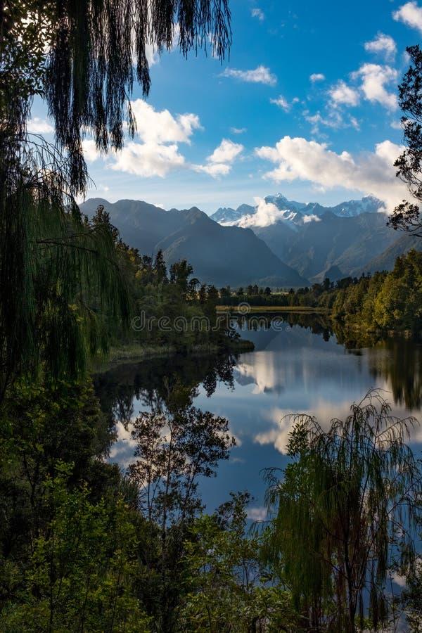 Una opinión del retrato enmarcada por el follaje del lago increíblemente hermoso Matheson, Nueva Zelanda con la reflexión del sur imagen de archivo libre de regalías