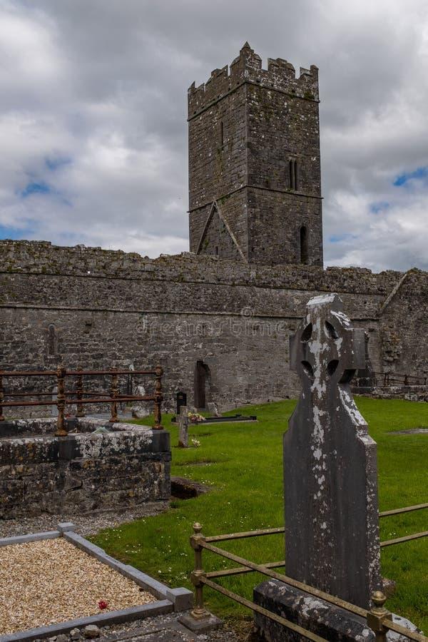 Una opinión del retrato a través de las piedras graves de las ruinas de Clare Abbey un exterior agustino Ennis, condado Clare del imagen de archivo