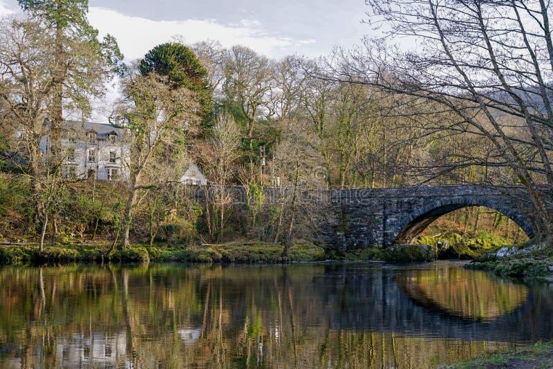 Una opinión reflexiva del lago rodeada por el bosque con una casa en la distancia foto de archivo libre de regalías