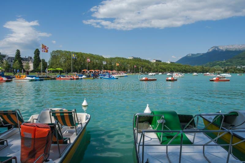 Una opinión soleada sobre el lago Annecy, Francia, con los barcos del pedal en el muelle y los turistas en el parque imagenes de archivo
