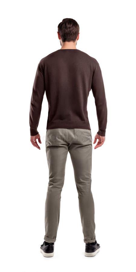 Una opinión trasera sobre un ajuste moderno y un hombre ocasional vestido que se coloca en una postura relajada totalmente recta imagen de archivo