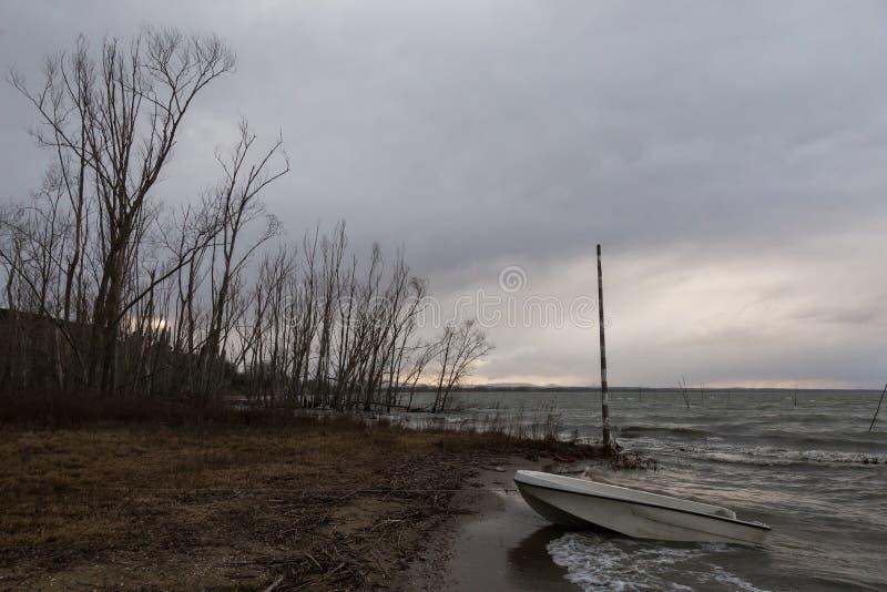 Una orilla del lago con los árboles, el clima tempestuoso, las nubes, las ondas de agua y un pequeño barco fotos de archivo