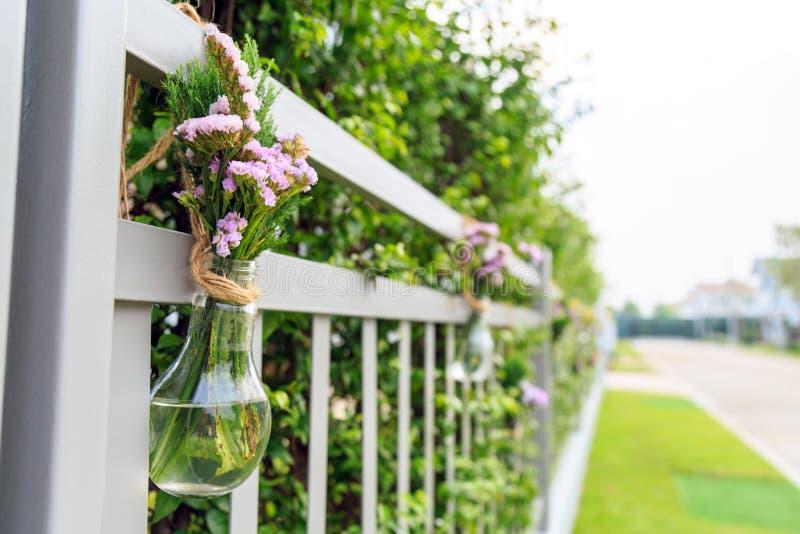 Una púrpura florece en la ejecución formada del florero de la bombilla en la cerca casera fotos de archivo libres de regalías