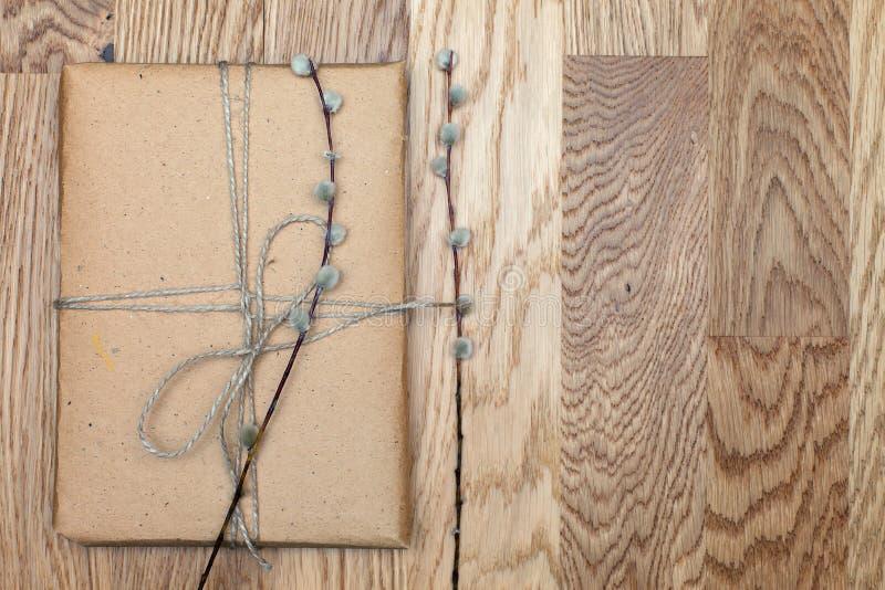 Una pacchetto o scatola in carta di eco sulla tavola di legno Vista superiore Contenitore di regalo legato con cordicella fotografia stock libera da diritti