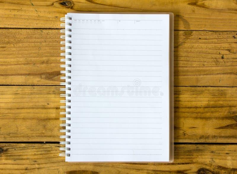 Una pagina in bianco del taccuino sulla vista superiore del taccuino di legno dell'ufficio della tavola per fotografia stock