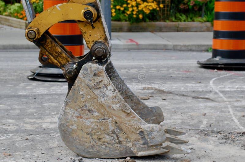 Una pala dell'escavatore si siede in ozio su una strada immagini stock