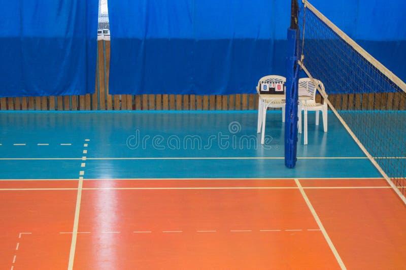 Una palestra vuota con una rete di pallavolo, le sedie ed il tabellone nella scuola fotografie stock