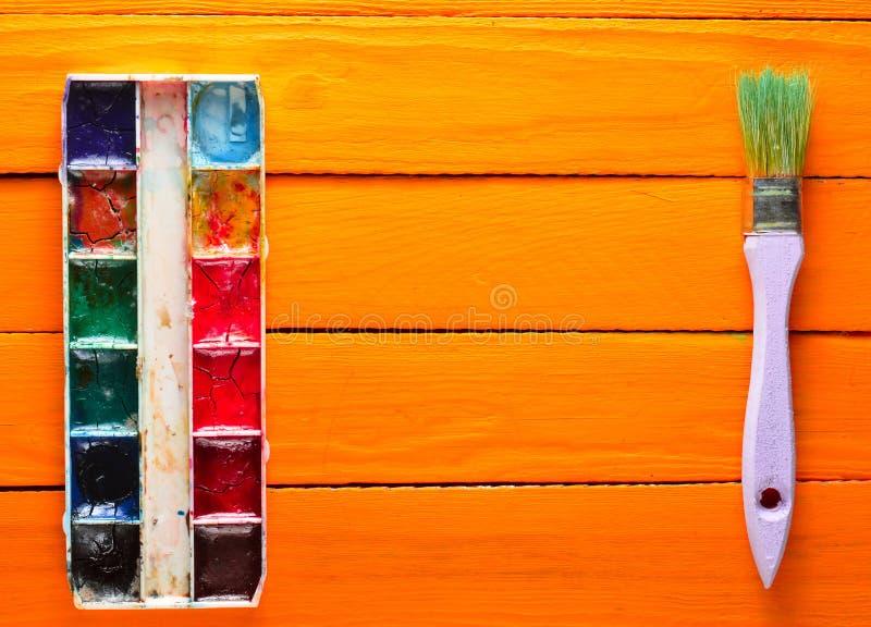 Una paleta de la pintura de la acuarela y un cepillo para pintar en los tableros de madera Pintura para pintar madera