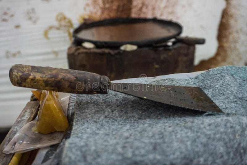 Una paleta sucia para la cera de limpieza de los restos en la cacerola grande Pekalongan admitido foto Indonesia fotografía de archivo libre de regalías
