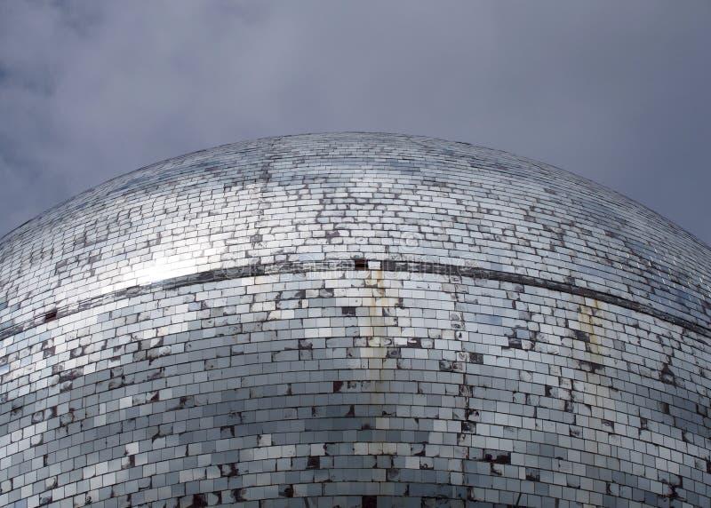 Una palla all'aperto dello specchio fatta di migliaia di pezzi di vetro che riflettono un'immagine spezzettata di un cielo nuvolo fotografia stock libera da diritti