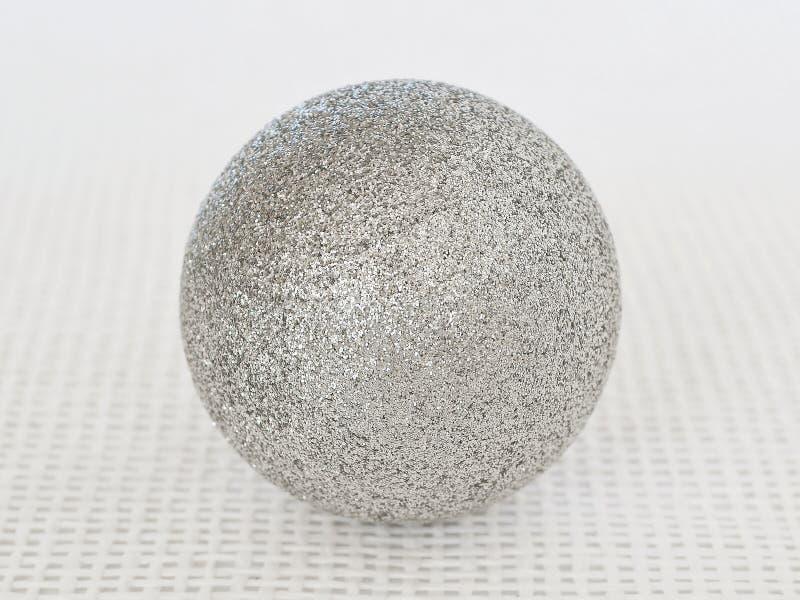 Una palla d'argento brillante di natale con le scintille su un fondo strutturale bianco fotografia stock