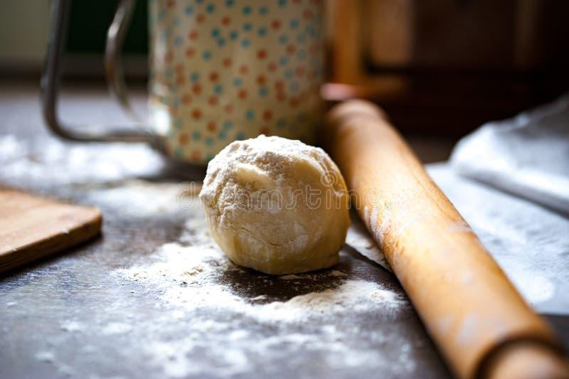 Una palla di pasta spruzzata con il dus della farina, del matterello e del fiore fotografia stock