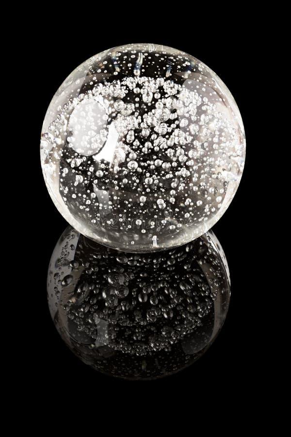 Una palla di vetro con le bolle interne su una superficie nera dello specchio fotografia stock - Le regole dello specchio ...