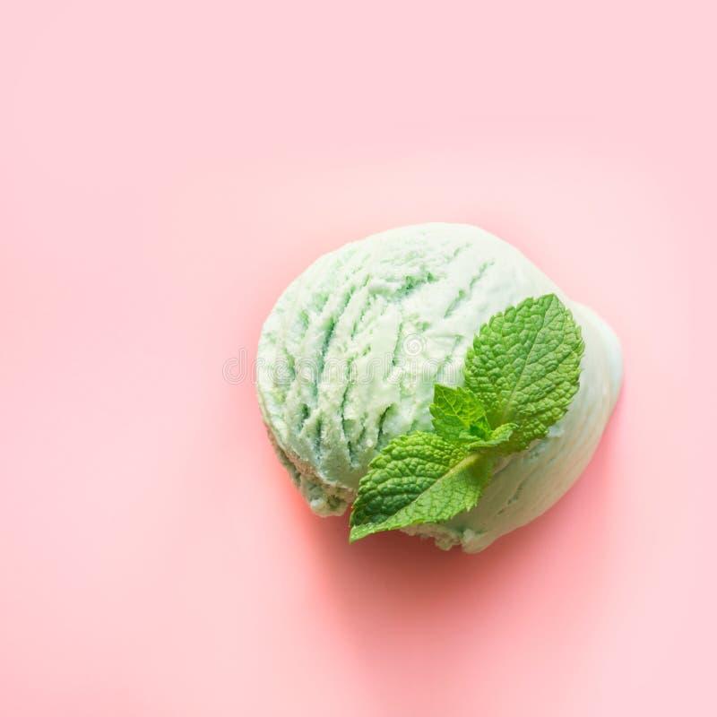 Una palla verde del gelato del tè di matcha o del pistacchio con la menta su fondo rosa Vista da sopra immagine stock libera da diritti