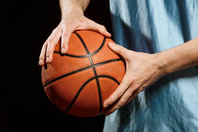 Una pallacanestro in mani del giocatore fotografie stock
