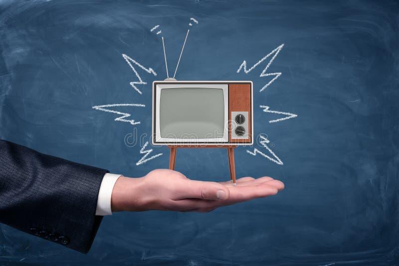 Una palma del ` s dell'uomo d'affari tiene una piccola retro TV con le gambe e l'antenna sul fondo della lavagna fotografia stock