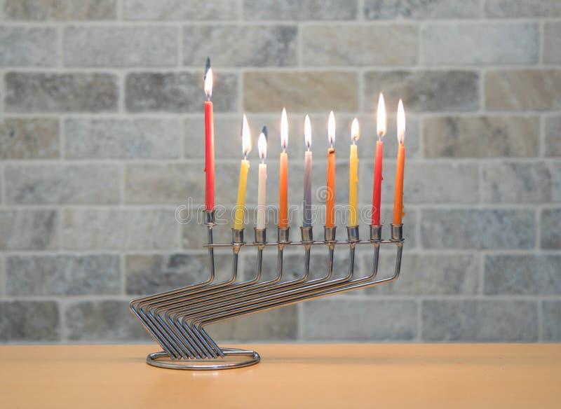 Una palmatoria del metal para la celebración de Jánuca se opone con las velas encendidas en la tabla al contexto de una pared de  imagen de archivo libre de regalías