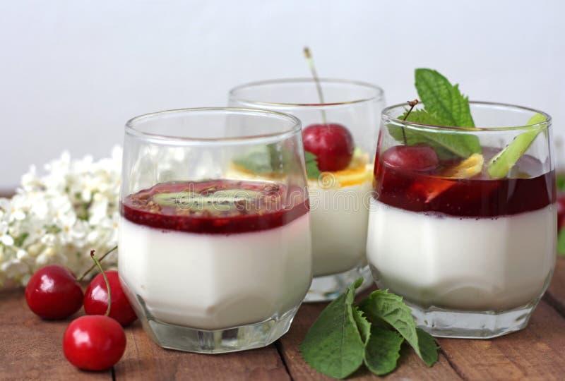 Una panna cotta di tre dessert con la ciliegia e la menta del KIWI su superficie di legno immagini stock