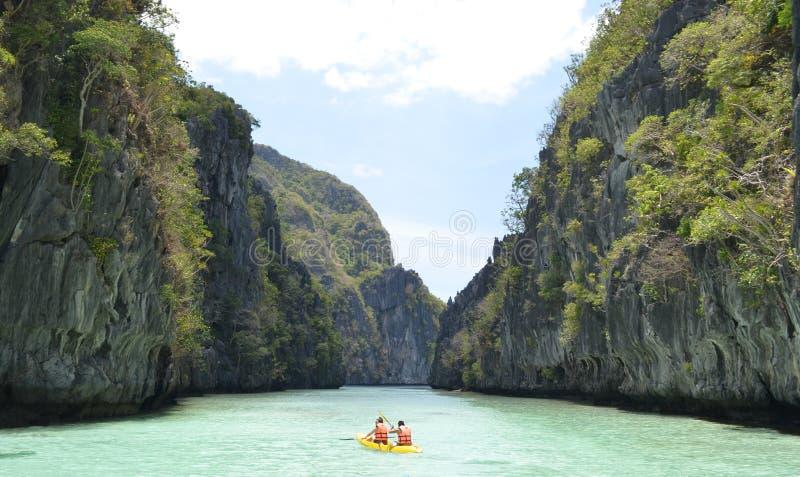 Una panoramica di due maschi che remano una barca in maglie di vita sulla bella isola di EL Nido nelle Filippine immagini stock