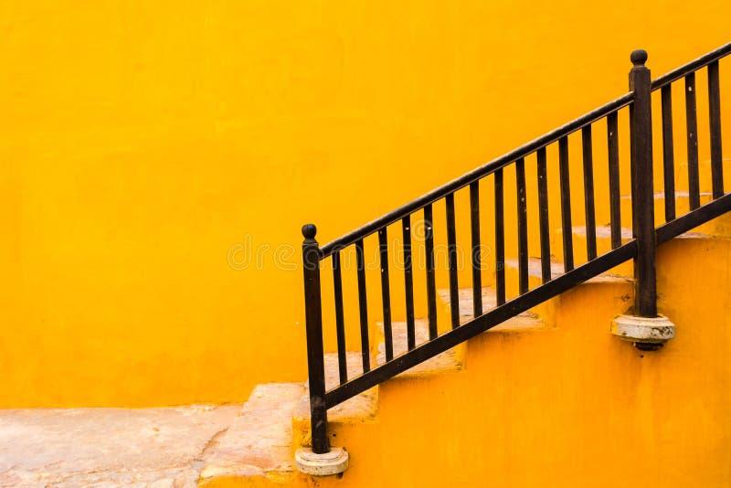 Una pared amarilla con las escaleras imagenes de archivo