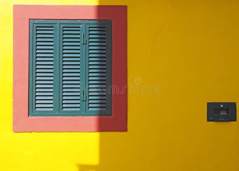una pared amarilla vibrante con el marco rojo y colores portugueses t?picos shuttered cerrados verdes de la ventana en luz del so fotos de archivo