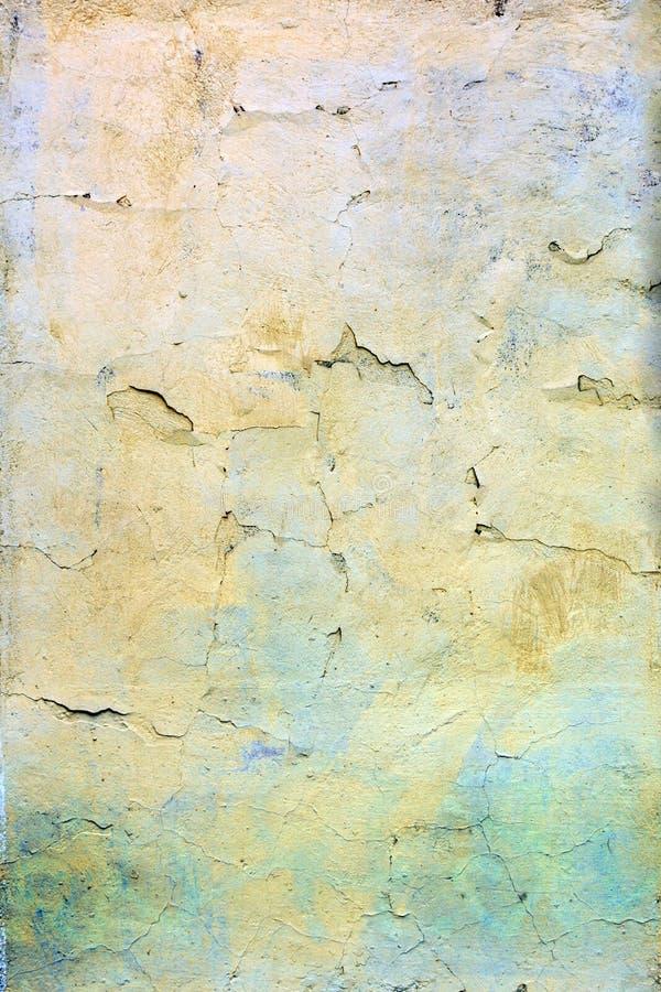 Una pared con la pintura amarilla y azul agrietada Fondo hermoso Textura de la vieja cubierta con las grietas imagen de archivo libre de regalías