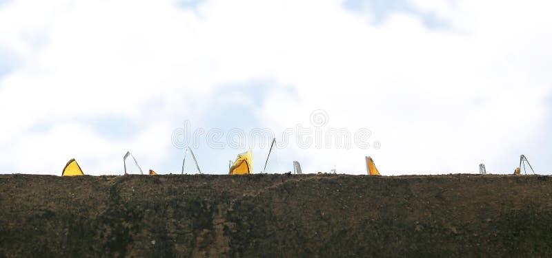 Una pared de la barricada cubierta con el vidrio quebrado contra fondo del cielo imagen de archivo libre de regalías