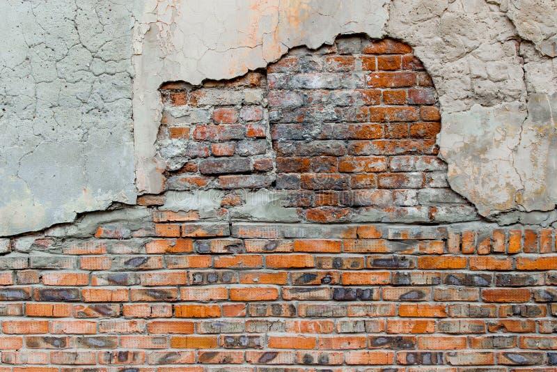 Una pared de ladrillo dañada vieja cubierta parcialmente con el viejo plasterwork agrietado imagen de archivo