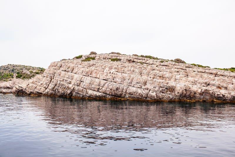 Una pared de piedra grande de la piedra beige en el mar imágenes de archivo libres de regalías