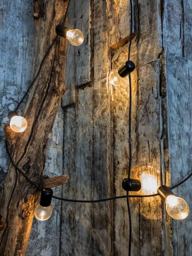 Una pared de tableros ligeramente te?idos, una guirnalda de bombillas en un tronco de ?rbol en el cuarto Bombillas calientes amar fotos de archivo libres de regalías