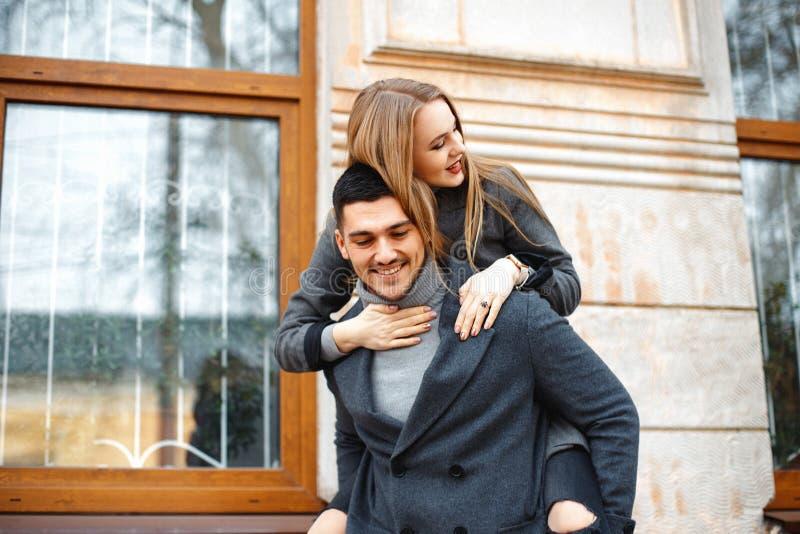 Una pareja amorosa camina en un abrigo por la calle foto de archivo libre de regalías