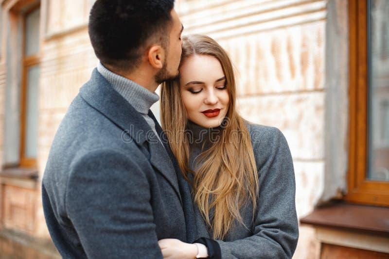 Una pareja amorosa camina en un abrigo por la calle imagen de archivo libre de regalías
