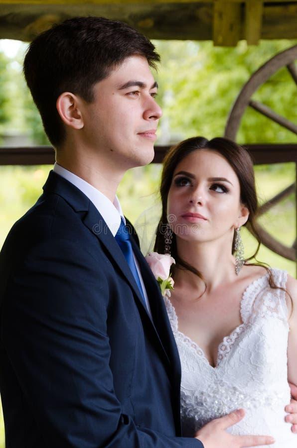 Una pareja casada hermosa en los vestidos de boda, presentando para un tiroteo de foto en un pueblo bielorruso Fondo verde fotos de archivo