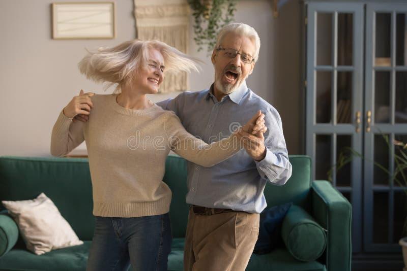 Una pareja de edad activa y despreocupada bailando riendo en el salón fotografía de archivo