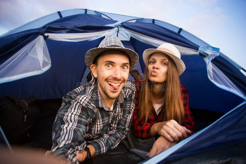 Una pareja divertida acampada tomando selfie. Amigos felices que tienen togheter de la diversi?n imagenes de archivo