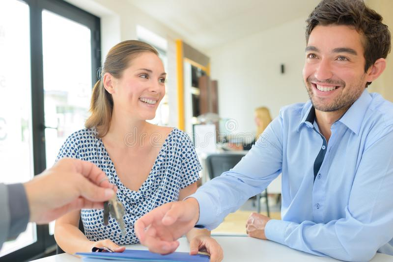 Una pareja feliz recibiendo claves del agente inmobiliario foto de archivo
