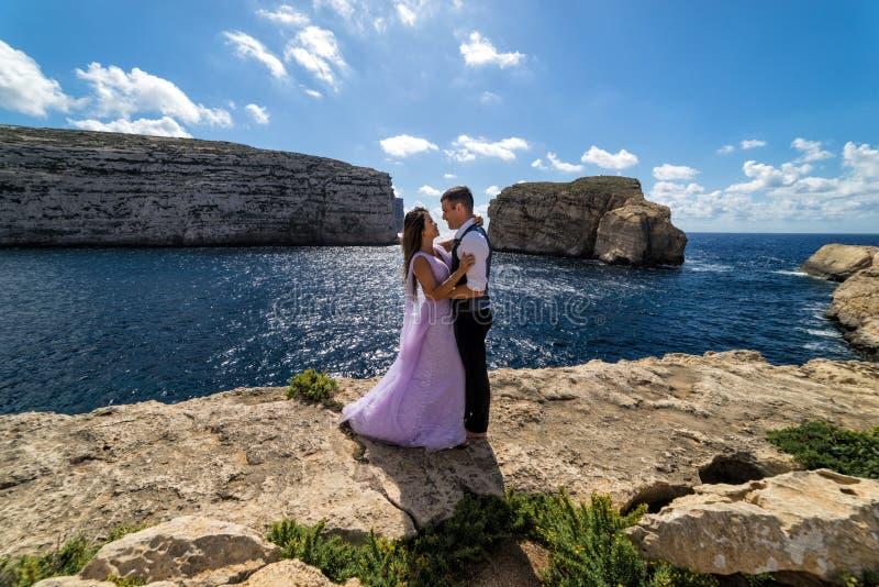 Una pareja que es casada en la costa rugosa de Gozo, Malta imagenes de archivo
