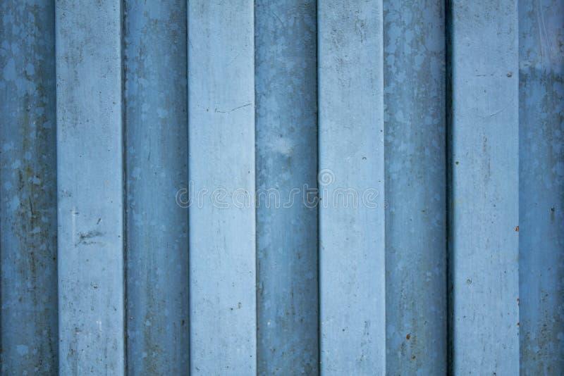 Una parete blu bianca del metallo Righe verticali macchie della ruggine e della pittura fotografia stock libera da diritti
